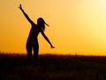 Silhouette of  happy young girl in field.